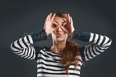 Buy stock photo Studio portrait of a cheerful young woman making a face with her hands while standing against a dark background