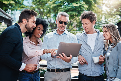 Buy stock photo Shot of a group of businesspeople working together on a laptop outdoors