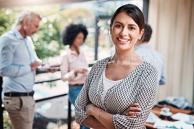 Buy stock photo Portrait of a confident young businesswoman standing outside with her colleagues in the background