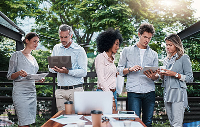 Buy stock photo Shot of a group of businesspeople working together outdoors