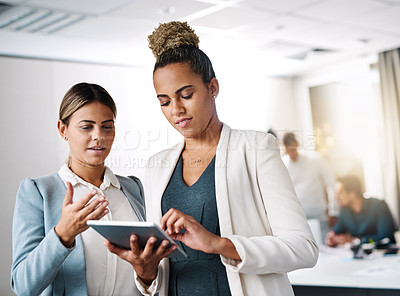 Buy stock photo Shot of two businesswomen working on a digital tablet in an office