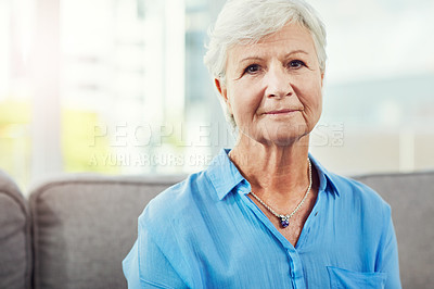 Buy stock photo Cropped portrait of a senior woman sitting on her sofa at home