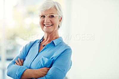Buy stock photo Cropped portrait of a senior woman standing with her arms folded at home