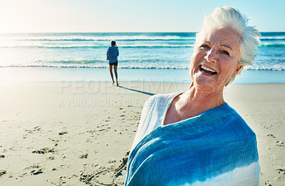 Buy stock photo Cropped portrait of a senior woman standing on the beach with her granddaughter in the background