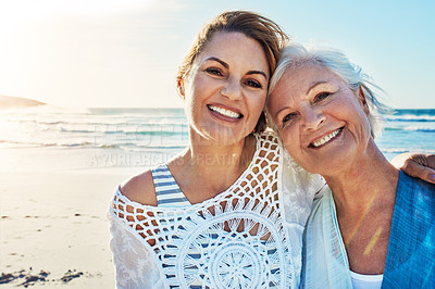 Buy stock photo Cropped portrait of a senior woman and her adult daughter spending a day at the beach