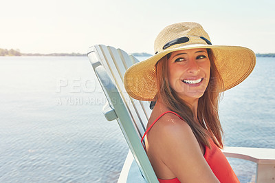 Buy stock photo Shot of a cheerful young woman wearing a hat while being seated on a chair next to a lake outside in the sun