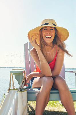 Buy stock photo Portrait of a cheerful young woman wearing a hat while being seated on a chair next to a lake outside in the sun