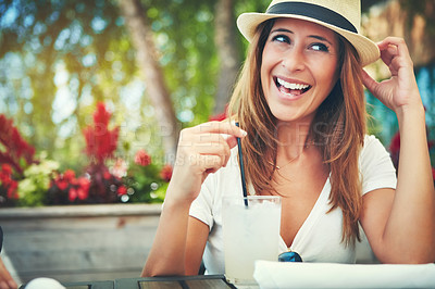 Buy stock photo Shot of a cheerful young woman wearing a hat and enjoying a cold beverage while being seated at a restaurant outside during the day