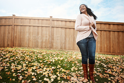 Buy stock photo Shot of a happy young woman in her backyard on an autumn's day