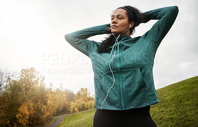 Buy stock photo Shot of an attractive young woman stretching while out for a run in nature