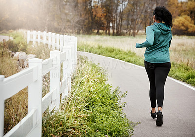Buy stock photo Rearview shot of a young woman going for a run in nature