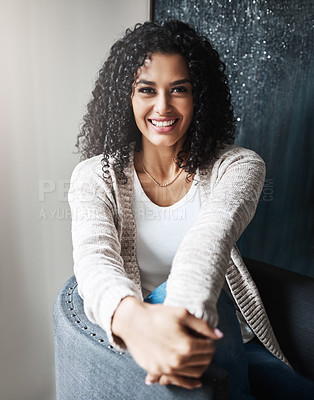 Buy stock photo Portrait of a cheerful young woman relaxing while being seated on a chair at home during the day