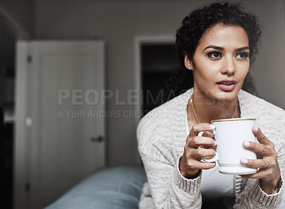 Buy stock photo Shot of a cheerful young woman drinking coffee while being seated on a couch inside at home during the day