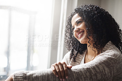 Buy stock photo Shot of a cheerful young woman relaxing while being seated on a chair at home during the day