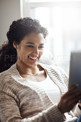 Buy stock photo Shot of an attractive young woman using a digital tablet at home
