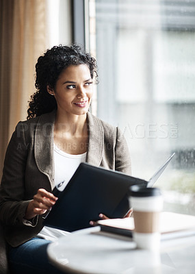 Buy stock photo Shot of a young businesswoman reading through a business folder in a cafe