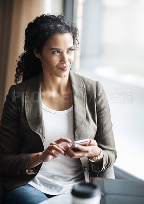 Buy stock photo Shot of a young businesswoman using a cellphone in a cafe