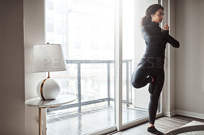 Buy stock photo Shot of a focused young woman doing a yoga pose from the comfort of home inside during the day