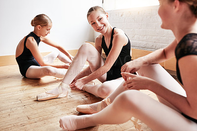 Buy stock photo Shot of a group of young girls putting on their ballet slippers in a dance studio
