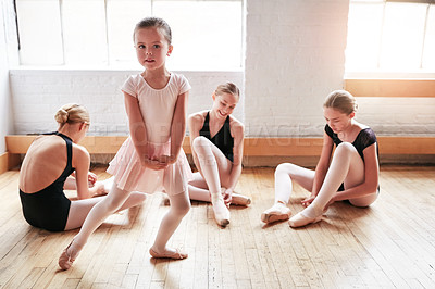 Buy stock photo Shot of an adorable little girl learning ballet with a group of older girls in a dance studio