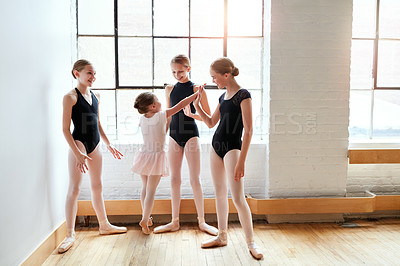 Buy stock photo Shot of a group of young ballerinas giving each other a high five in a dance studio