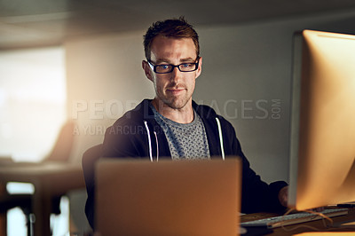Buy stock photo Shot of a young designer working late on a computer in an office
