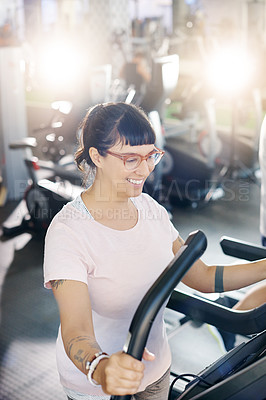 Buy stock photo Shot of a young woman exercising on a treadmill in a gym