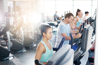 Buy stock photo Shot of a group of people exercising on treadmills in a gym