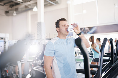 Buy stock photo Shot of a mature man drinking water while exercising on a treadmill in a gym