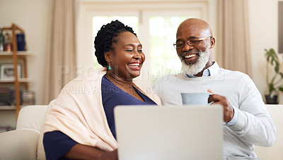 Buy stock photo Shot of a happy mature couple using a laptop together on the sofa at home