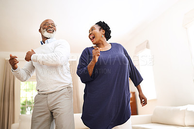 Buy stock photo Shot of a happy mature couple dancing together at home