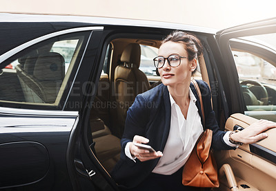 Buy stock photo Shot of a confident young businesswoman getting out of a car while holding a cellphone outside during the day