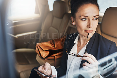 Buy stock photo Shot of a confident young businesswoman seated in a car as a passenger while busy on her phone and looking out of the window