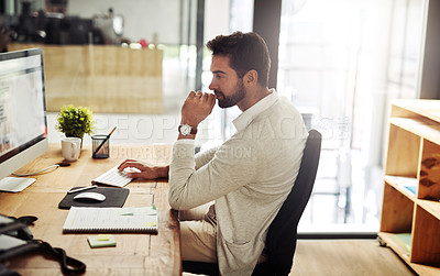Buy stock photo Shot of a handsome young businessman working late on a computer in an office