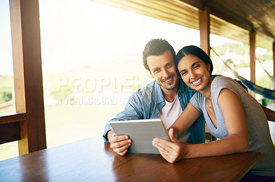 Buy stock photo Cropped shot of an attractive young married couple using a tablet together at home