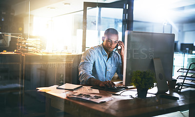 Buy stock photo Shot of a young businessman using a mobile phone during a late night in a modern office