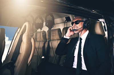 Buy stock photo Shot of a mature businessman using a headset while traveling in a helicopter