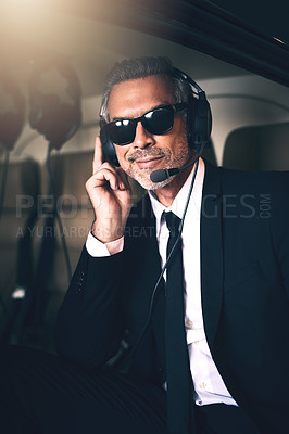 Buy stock photo Portrait of a mature businessman using a headset while traveling in a helicopter