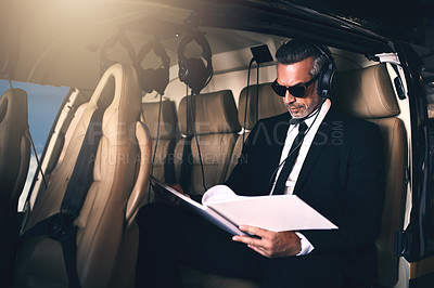 Buy stock photo Shot of a mature businessman reading through paperwork while traveling in a helicopter