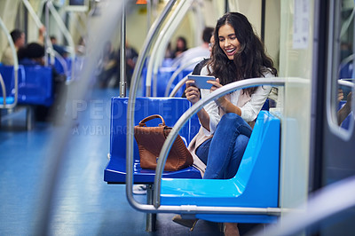 Buy stock photo Cropped shot of a young attractive woman using a cellphone while commuting with the train