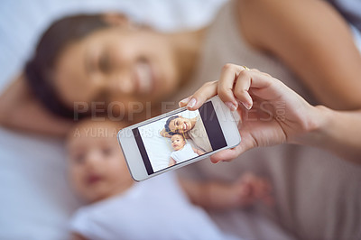 Buy stock photo Shot of a young woman taking selfies with her adorable baby boy at home