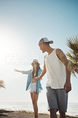 Buy stock photo Shot of a young man teaching his girlfriend how to skateboard on the promenade
