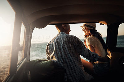 Buy stock photo Shot of an affectionate young couple enjoying a road trip along the coast