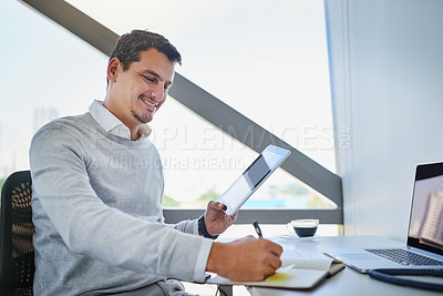 Buy stock photo Shot of a young businessman writing notes while working on a digital tablet in an office