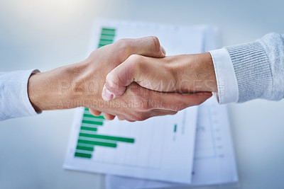 Buy stock photo Closeup shot of two businesspeople shaking hands over some paperwork in an office
