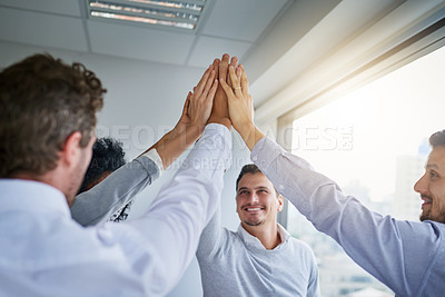 Buy stock photo Shot of a group of businesspeople high fiving in an office