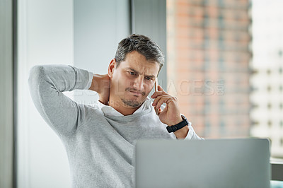 Buy stock photo Shot of a young businessman looking stressed out while talking on a cellphone in an office