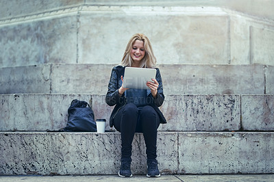Buy stock photo Shot of an attractive woman using a digital tablet in the city