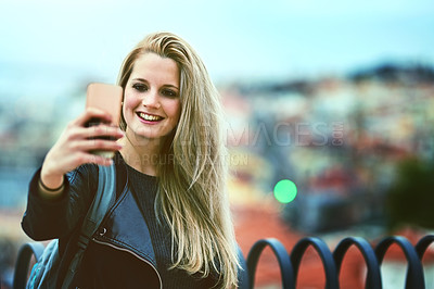 Buy stock photo Shot of a young woman using a cellphone to take selfies in the city