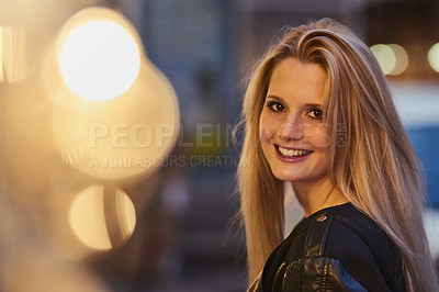 Buy stock photo Shot of a confident young woman out and about in the city at night